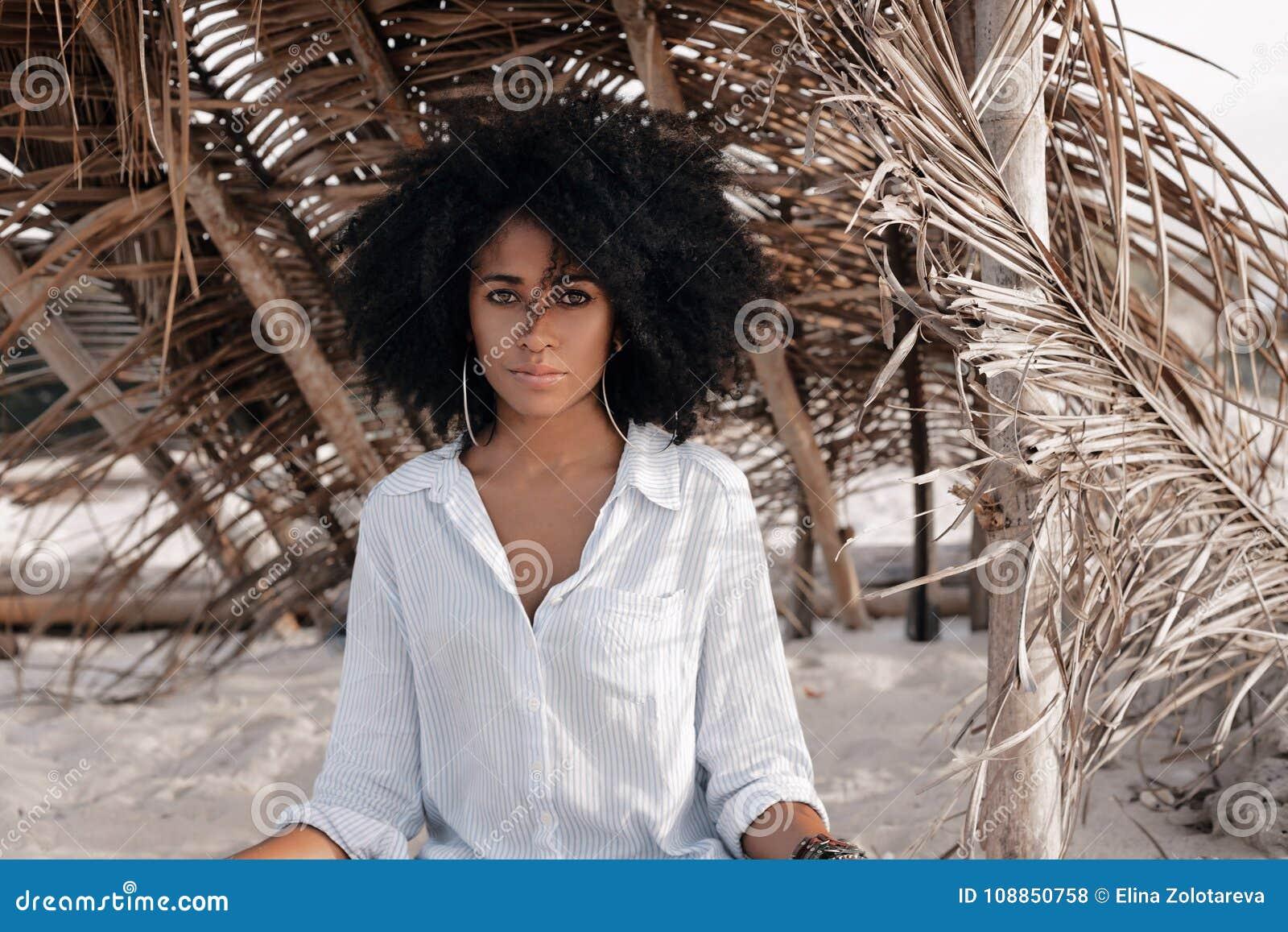 Mooie jonge Afrikaanse Amerikaanse meisjeszitting op zand bij bea