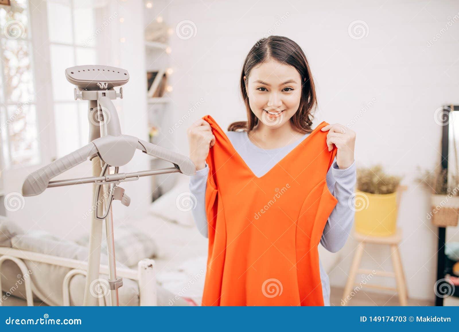Mooie jonge Aziatische vrouw die met kleren glimlachen die op kleding op het passen met modern in de ruimte proberen