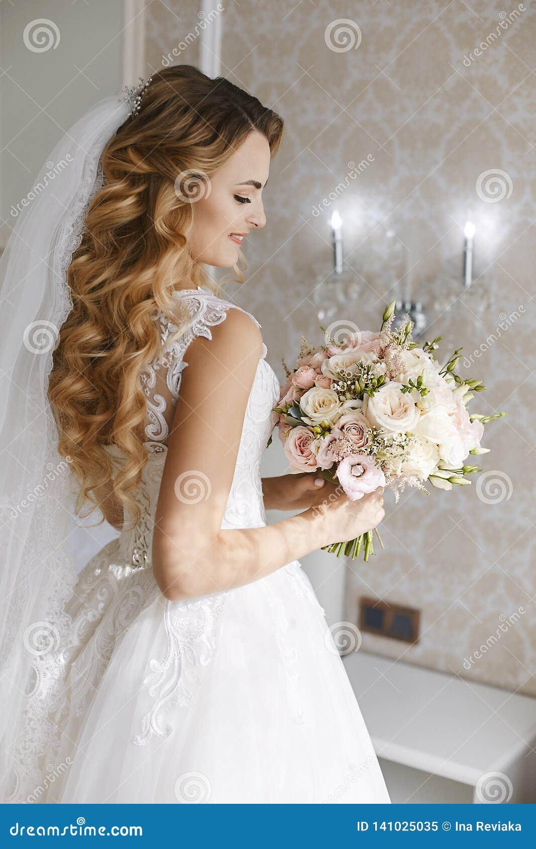 Mooie jonge blondebruid met modieus huwelijkskapsel in een witte modieuze kleding met een binnen boeket van bloemen