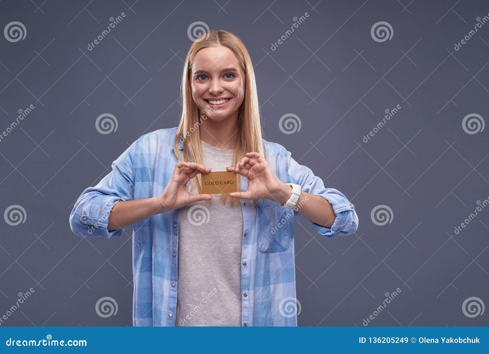 Mooie jonge dame die in blauw overhemd gouden kaart aantonen