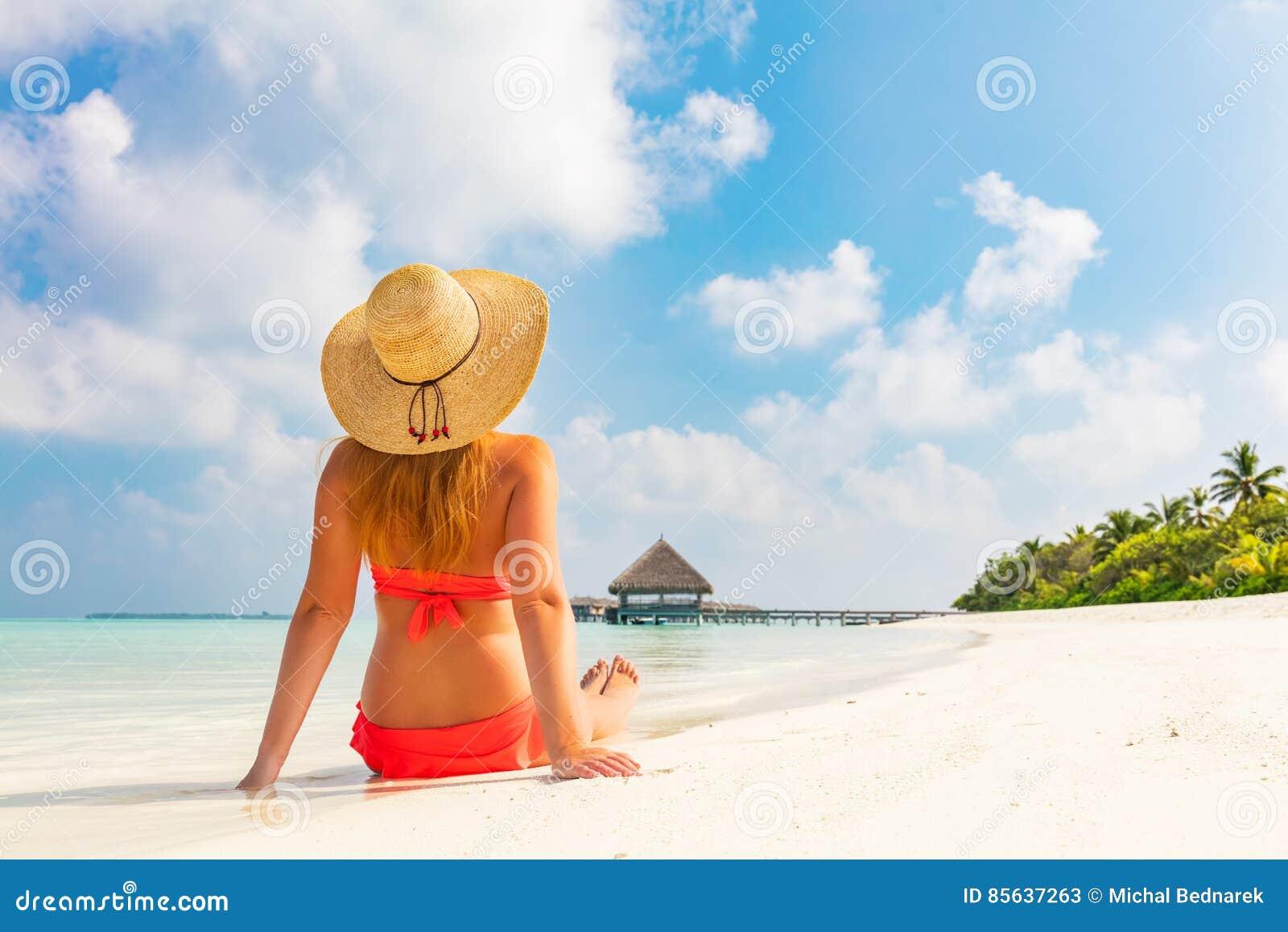 Mooie jonge die vrouw in sunhatzitting op tropisch strand in de Maldiven wordt ontspannen