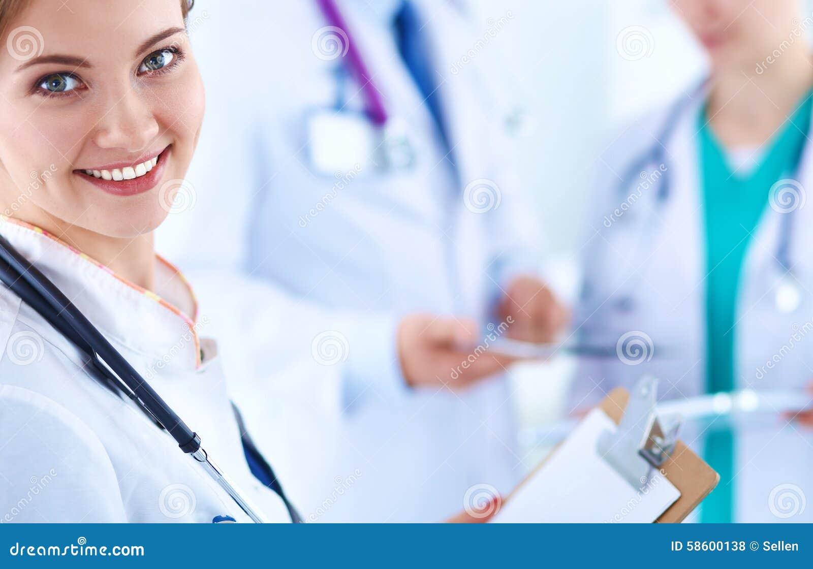 Mooie jonge het glimlachen vrouwelijke artsenzitting bij