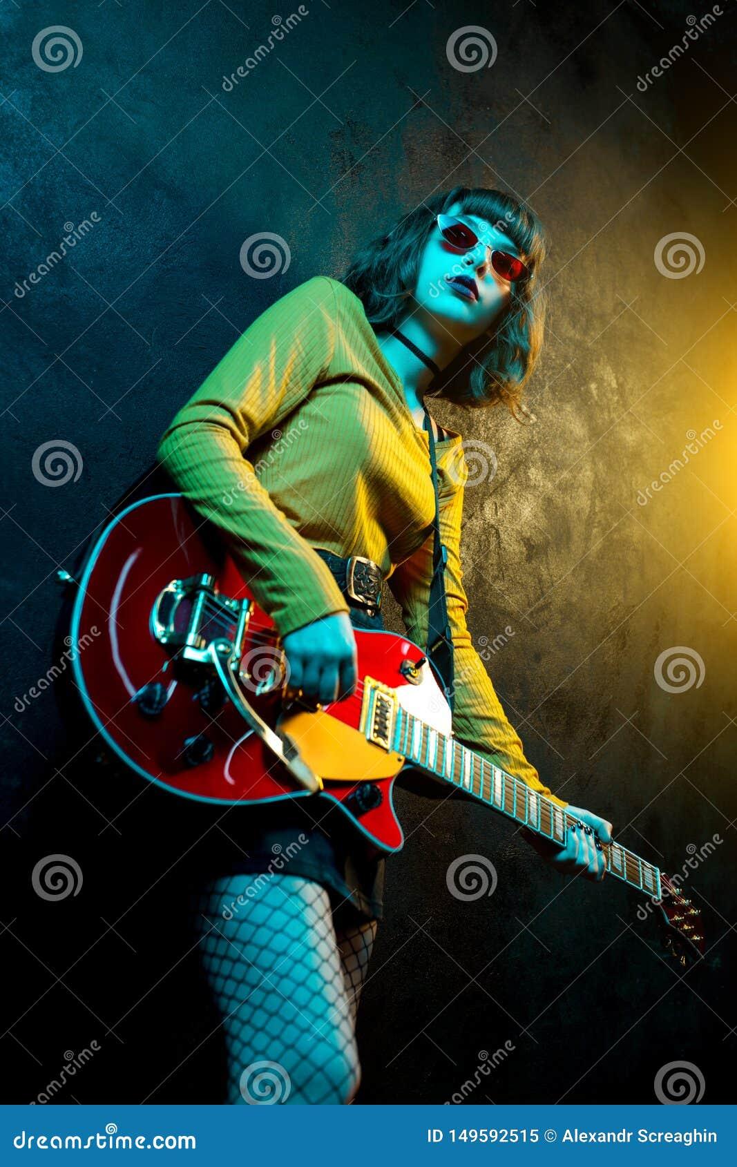 Mooie jonge hipstervrouw met krullend haar met rode gitaar in neonlichten De musicus van de rots speelt elektrogitaar