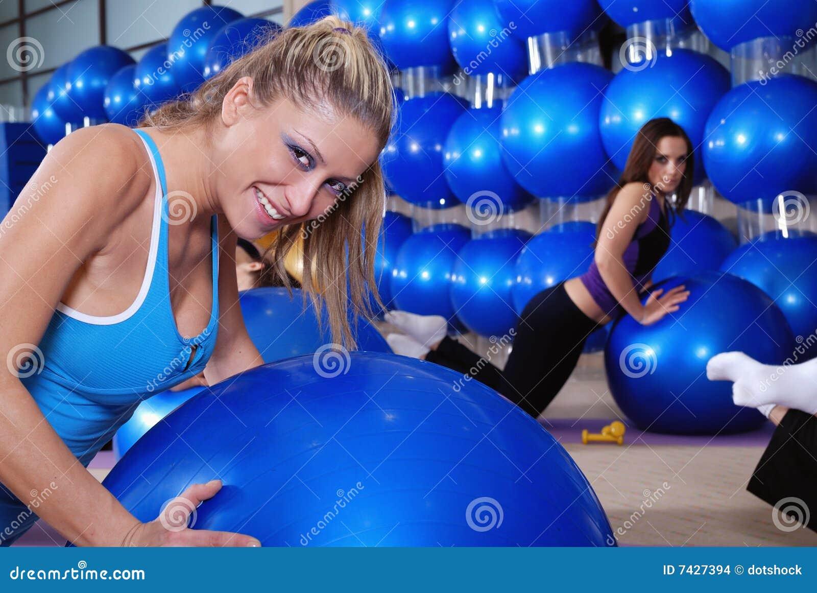 Mooie jonge meisjes die in een gymnastiek uitwerken