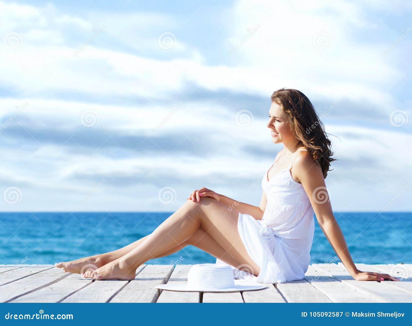 Mooie, jonge meisjeszitting op een pijler in een witte kleding De zomer, vakantie en reizend concept