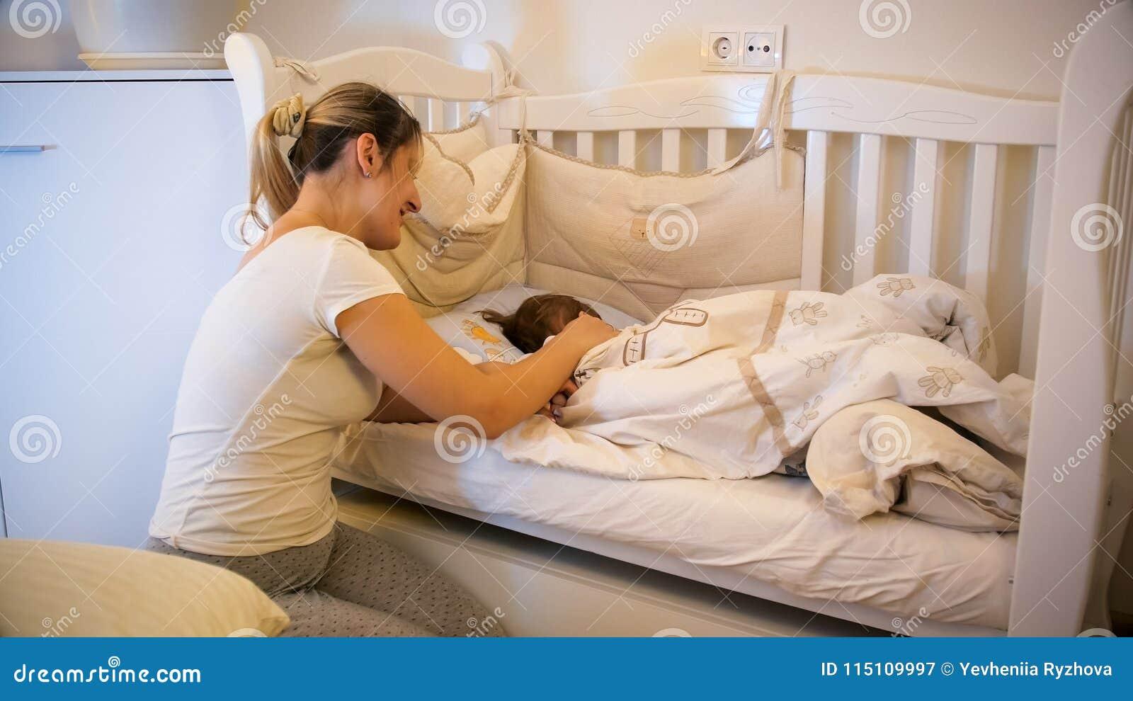 Mooie jonge moeder die in pyjama s haar leuke slaap van de peuterzoon in voederbak strelen bij kinderdagverblijf