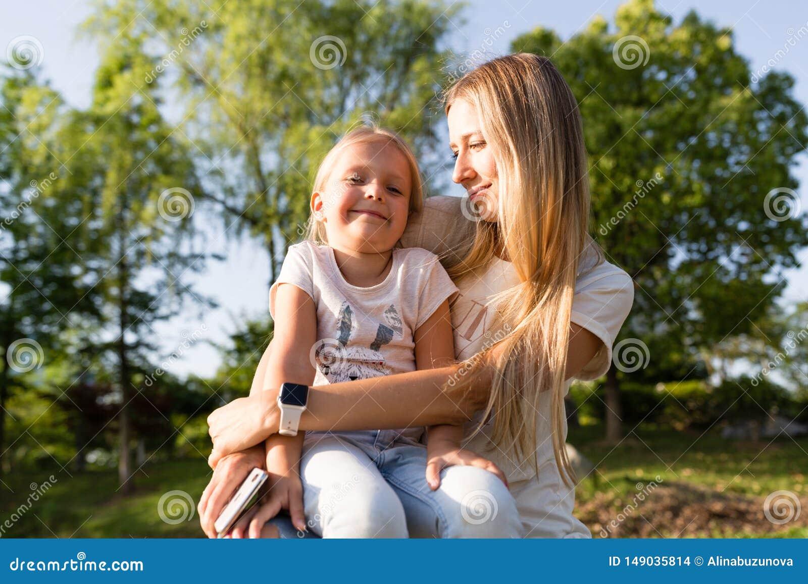 Mooie jonge moeder en dochter met blondehaar openlucht omhelzen Modieuze meisjes die het lopen in het park maken Het concept van