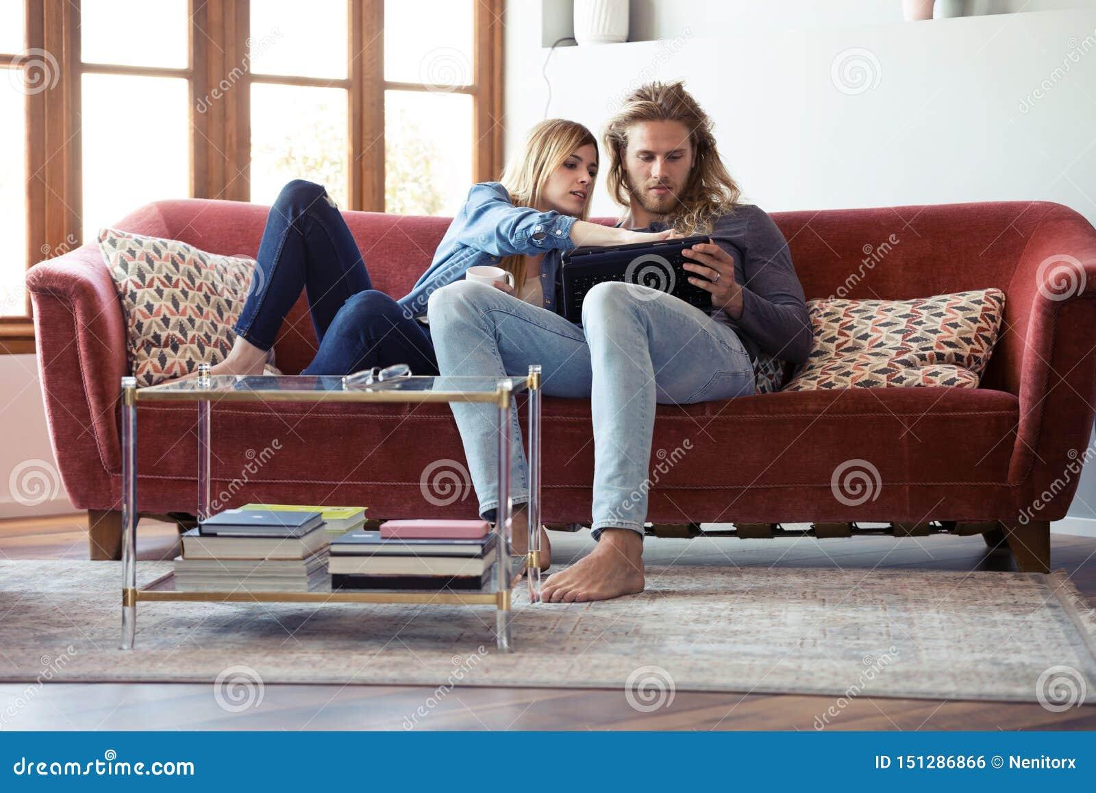 Mooie jonge paartekening met zij digitale tablet terwijl thuis het zitten op bank