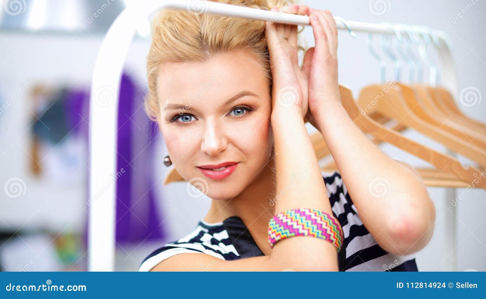 Mooie jonge stilist dichtbij rek met hangers in bureau