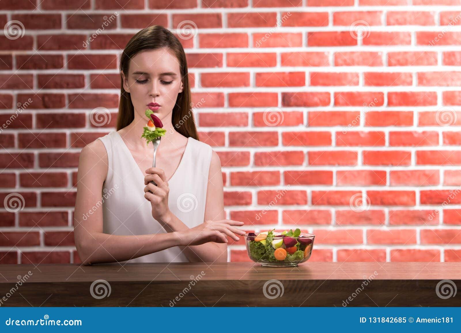 Mooie jonge vrouw in blije houdingen met de salade van de handholding
