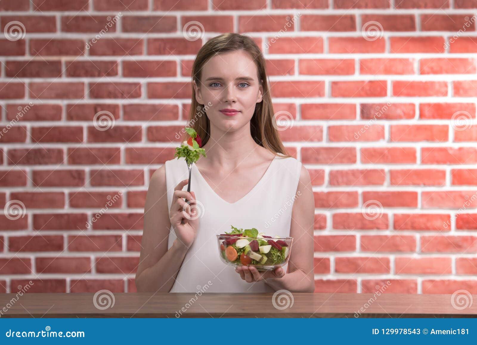 Mooie jonge vrouw in blije houdingen met de saladekom van de handholding