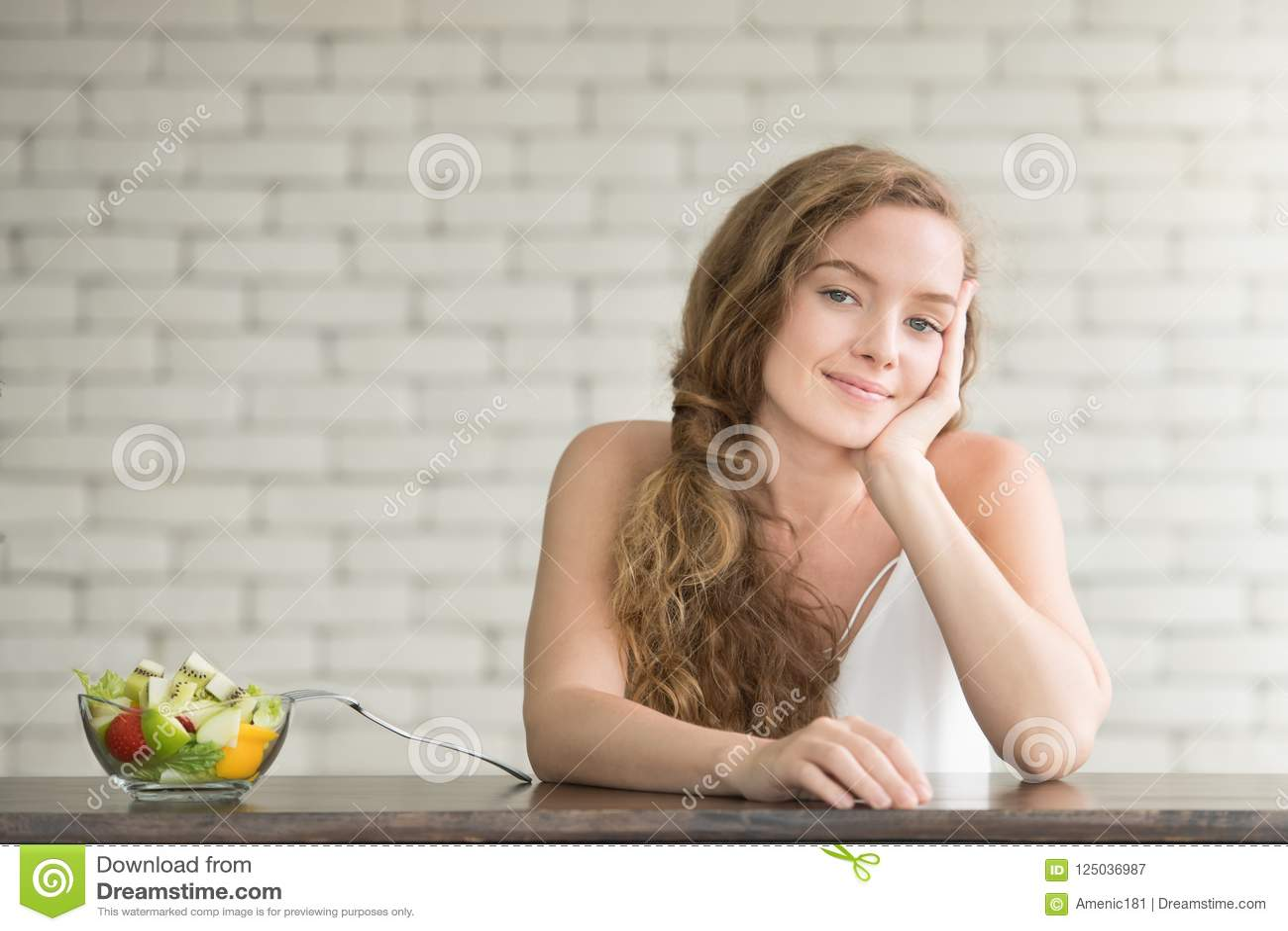 Mooie jonge vrouw in blije houdingen met saladekom
