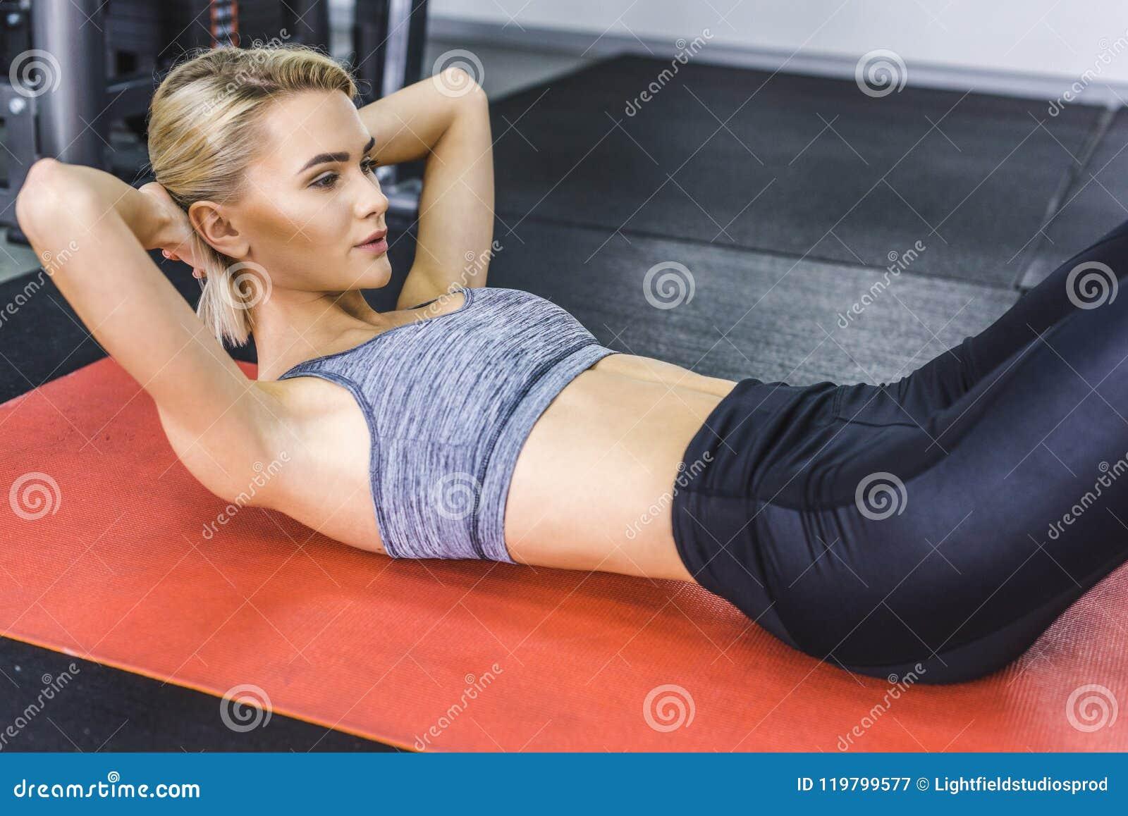 Mooie jonge vrouw die abs kraken op yogamat doen