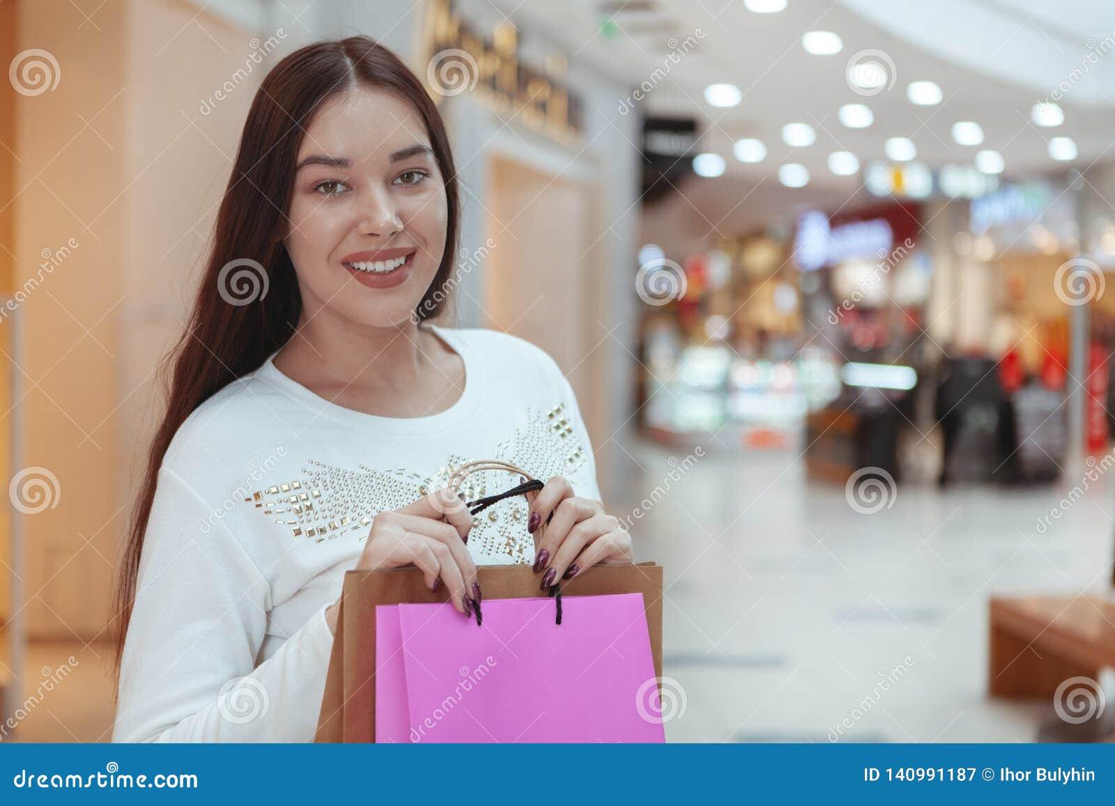 Mooie jonge vrouw die bij de lokale wandelgalerij winkelen