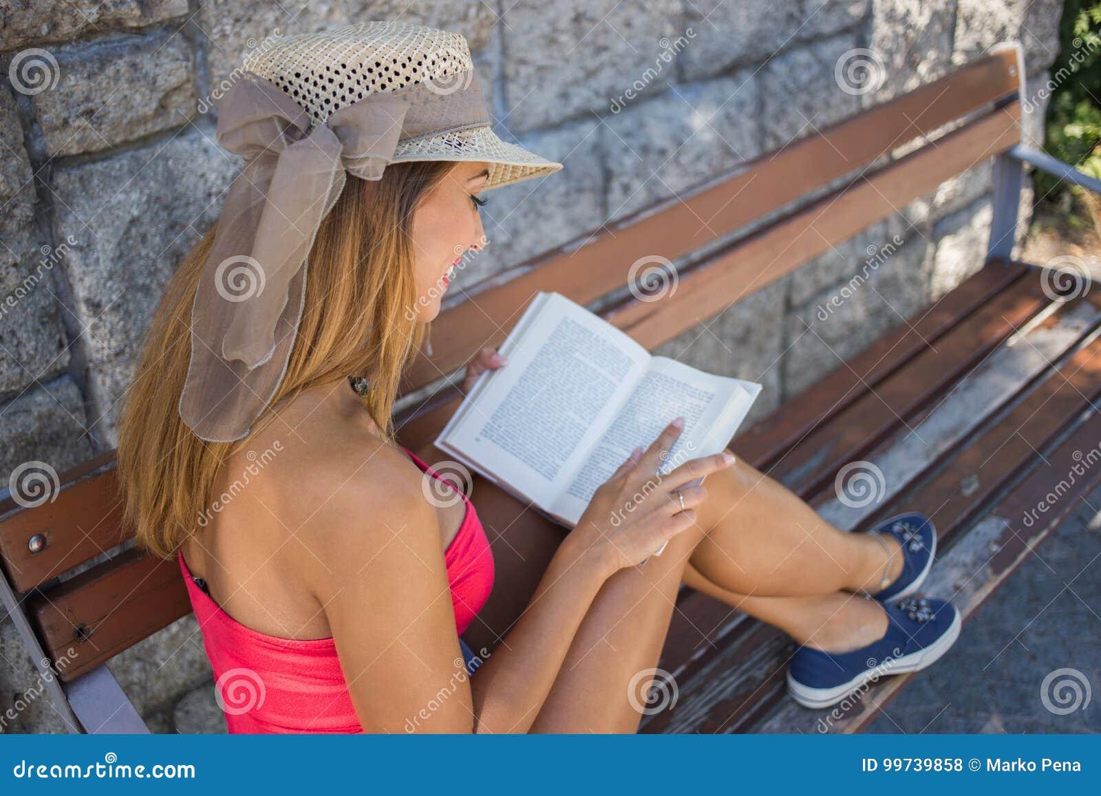 Mooie jonge vrouw die een boek op een bank lezen