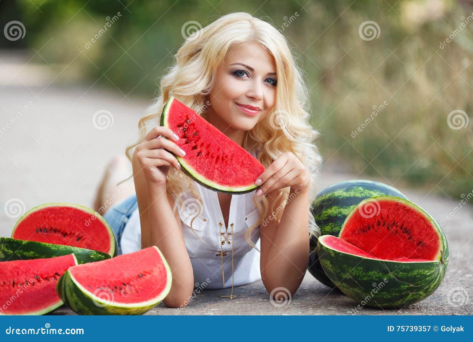 Mooie jonge vrouw die een plak van rijpe watermeloen houden