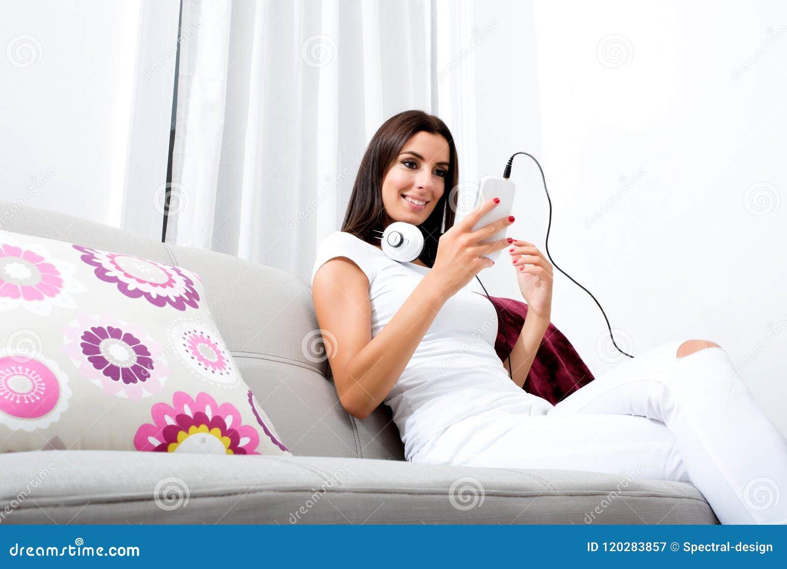 Mooie jonge vrouw die in hoofdtelefoons aan muziek luisteren