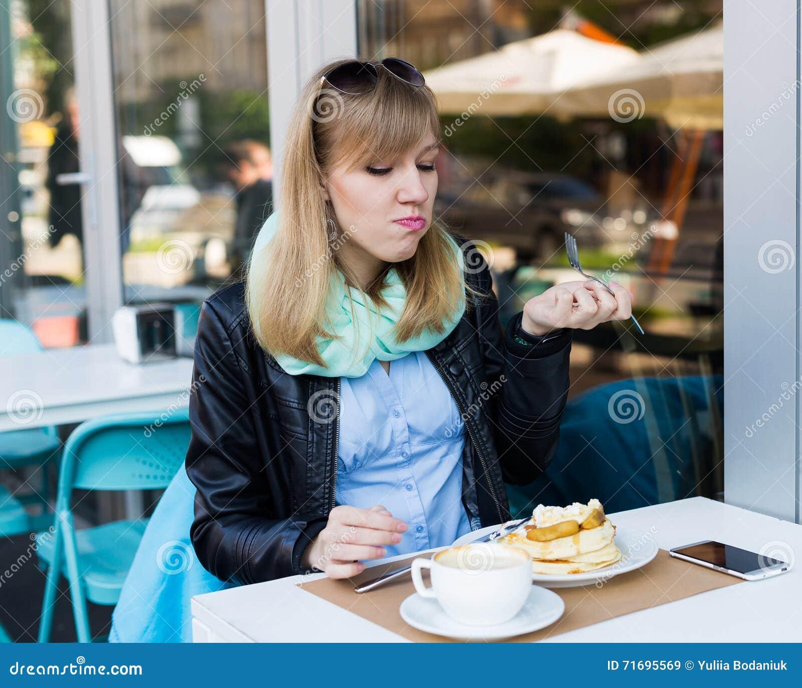 Mooie jonge vrouw die ontbijt eet