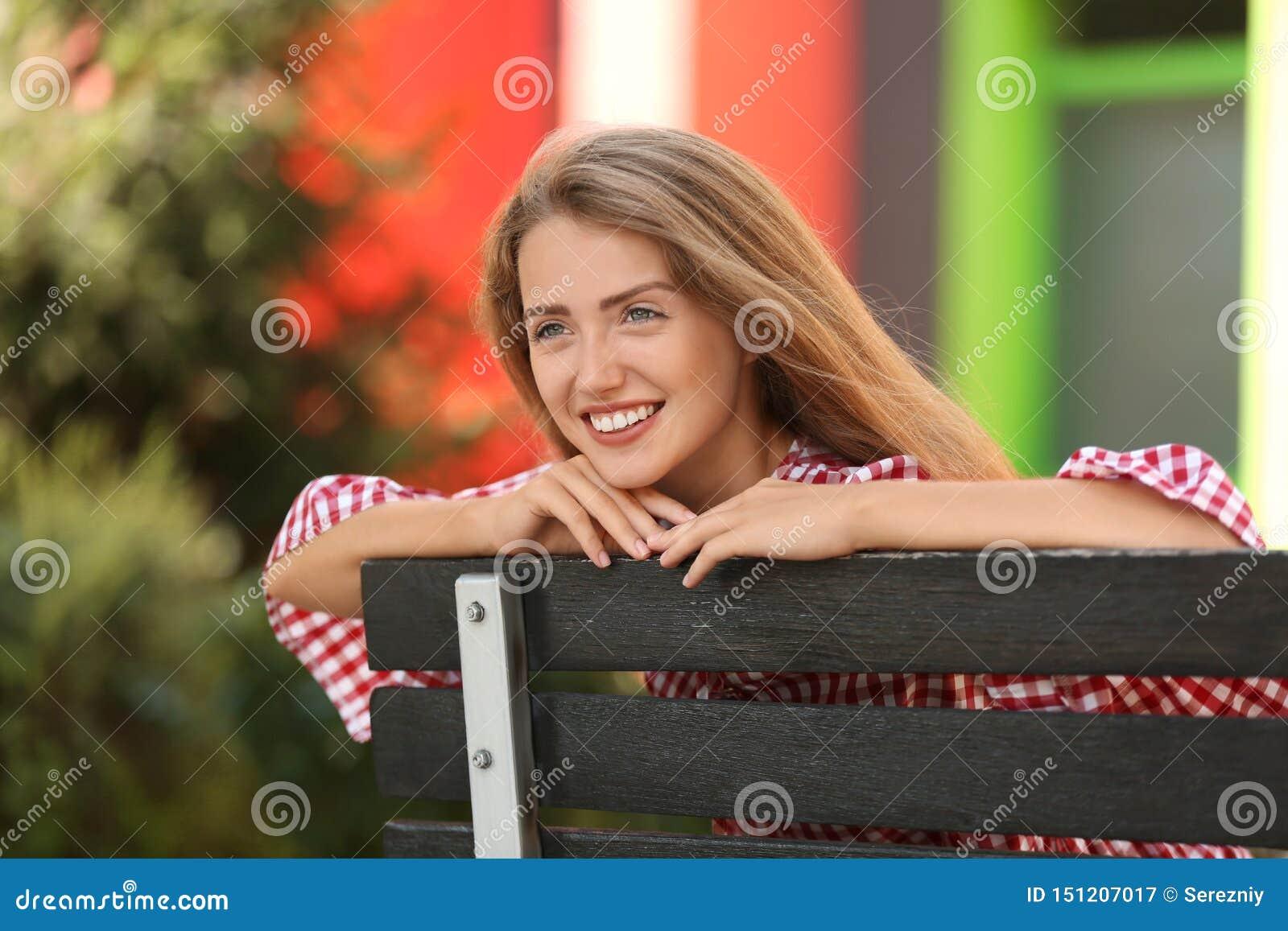 Mooie jonge vrouw die op houten bank in openlucht rust
