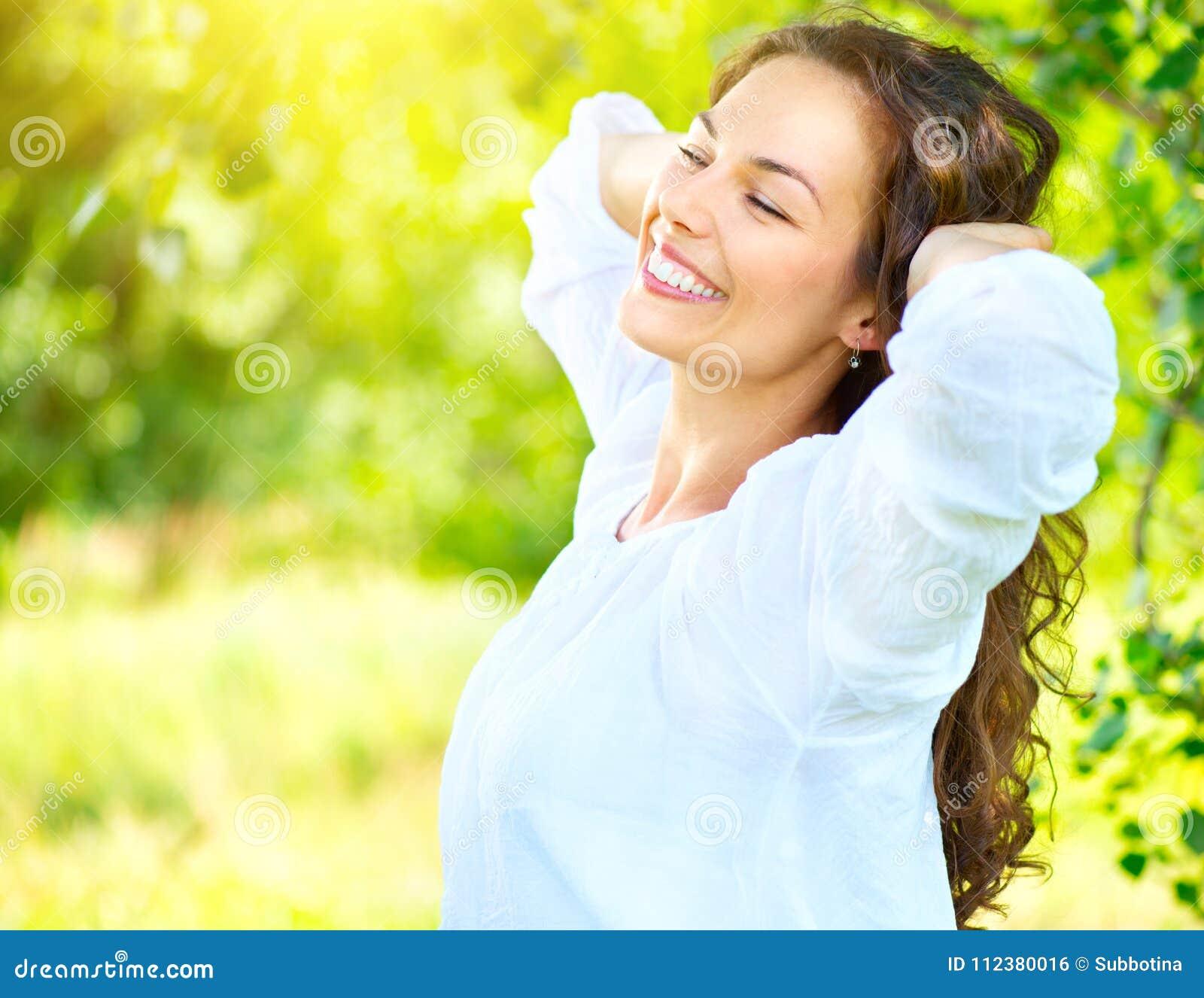 Mooie jonge vrouw die van aard genieten openlucht Het gelukkige het glimlachen donkerbruine meisje ontspannen in het de zomerpark