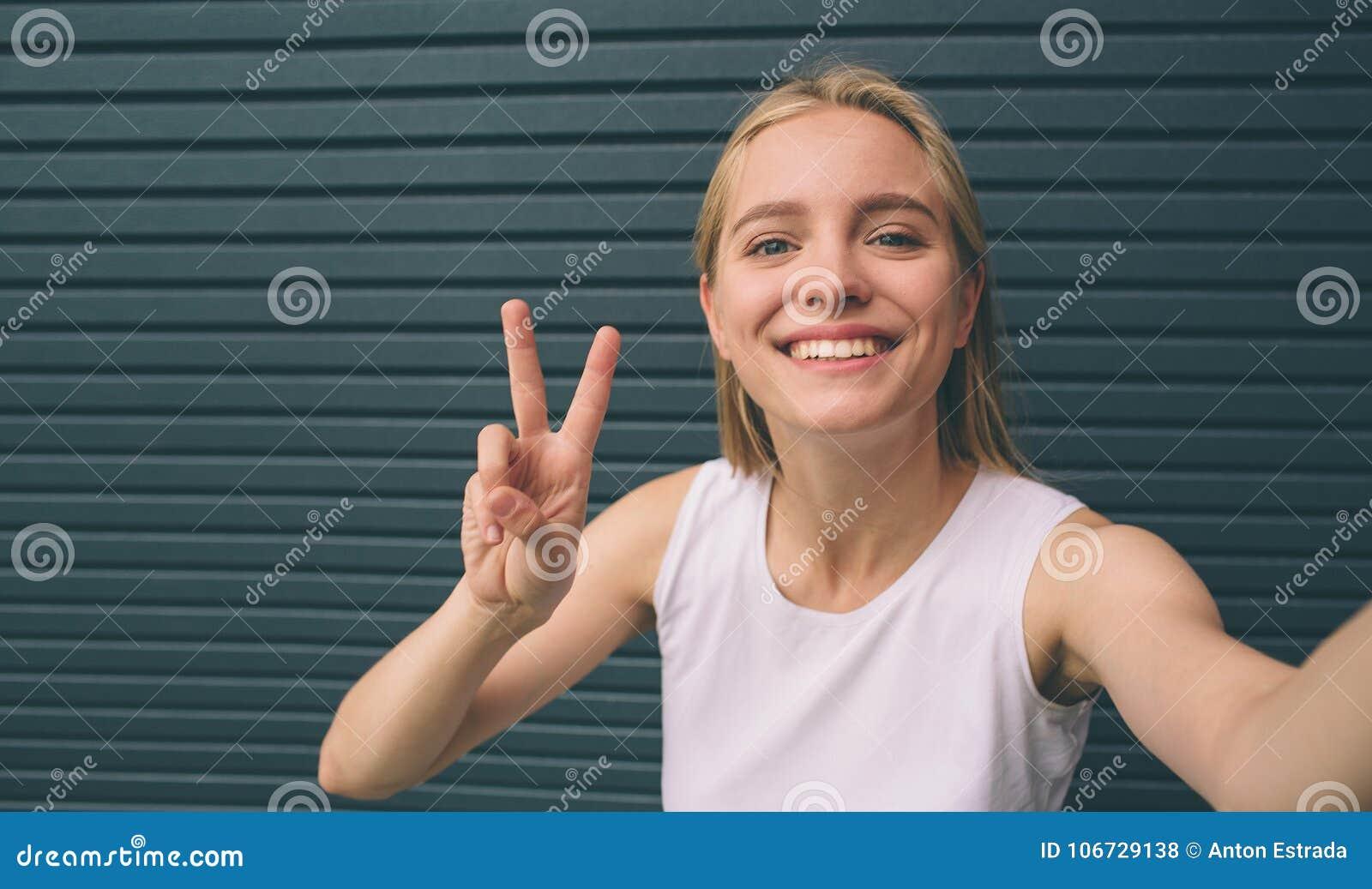 Mooie jonge vrouw die zelf-portret op een smartphone op een muurachtergrond maken