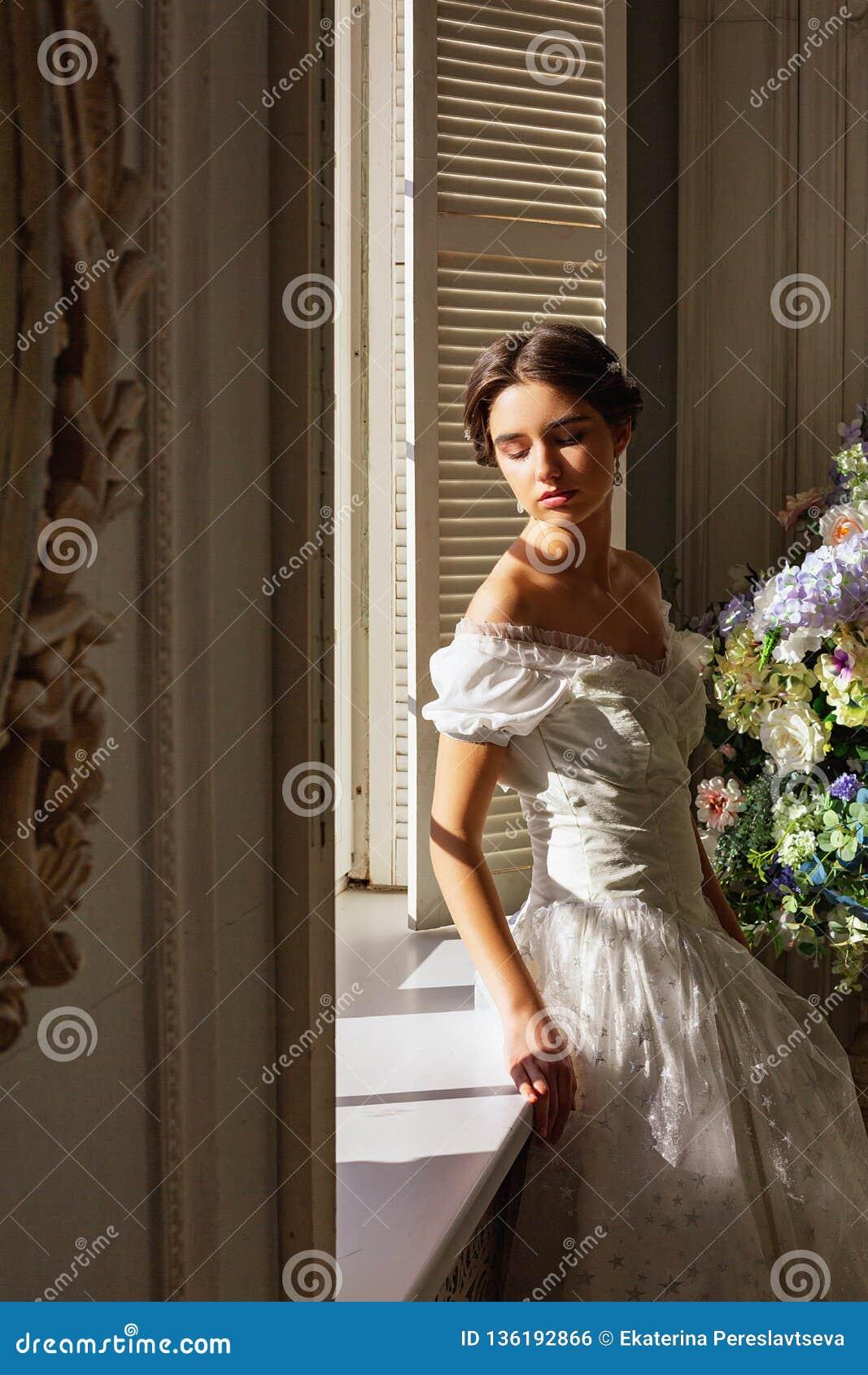 Mooie jonge vrouw die zich in witte kleding dichtbij spiegel bevinden