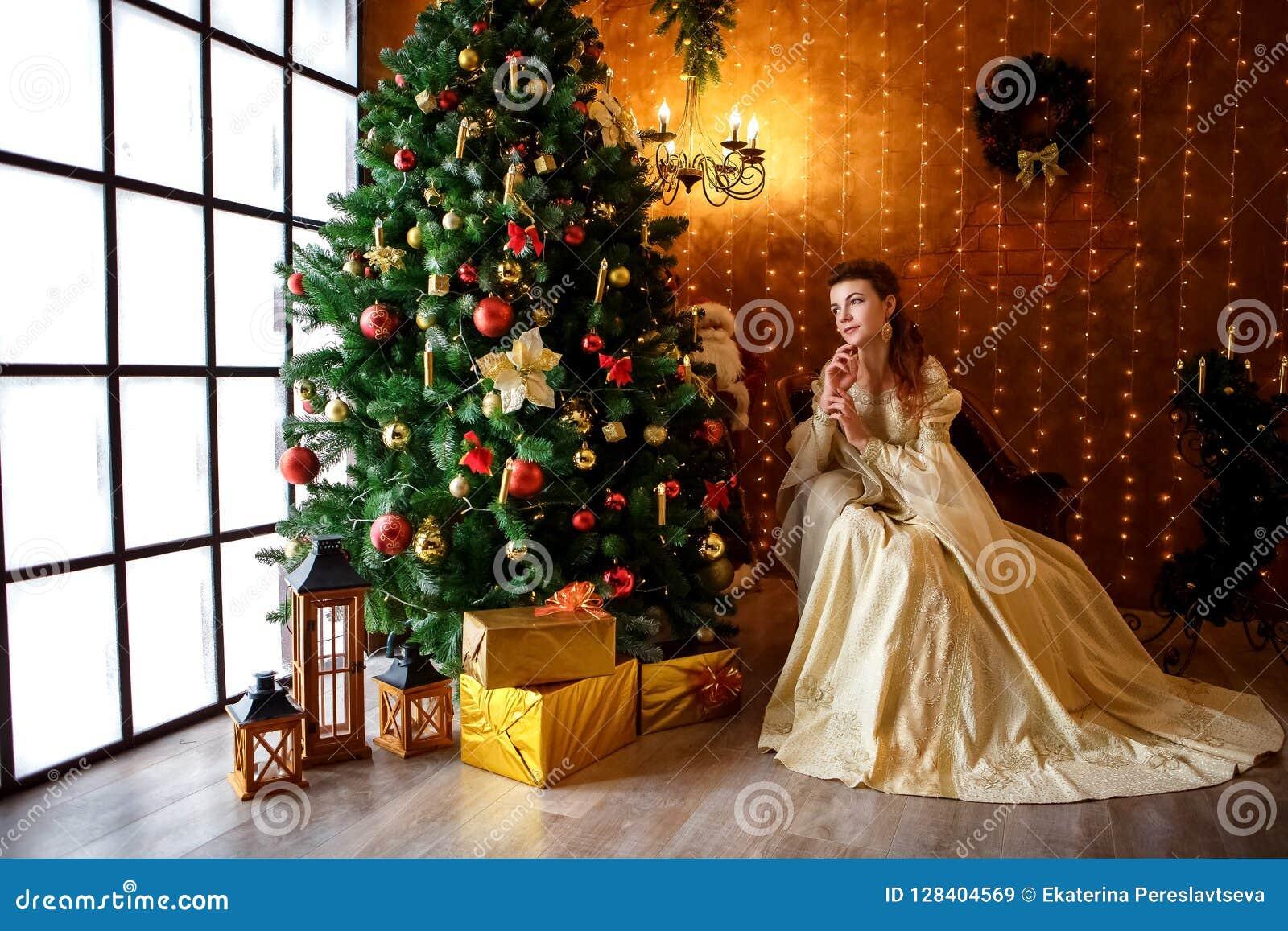 Mooie jonge vrouw in een mooie kledingszitting bij de Kerstboom met giften, Kerstmis en nieuw jaar