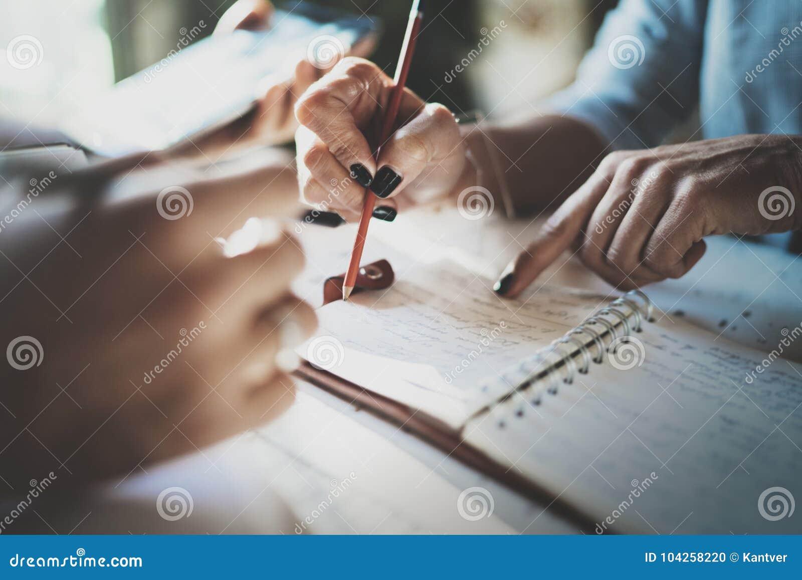 Mooie jonge vrouw en haar partner die iets in notastootkussen schrijven terwijl het zitten op leunstoel bij woonkamer charming