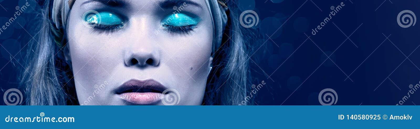 Mooie jonge vrouw met blauwe samenstelling Geïsoleerd op blauw