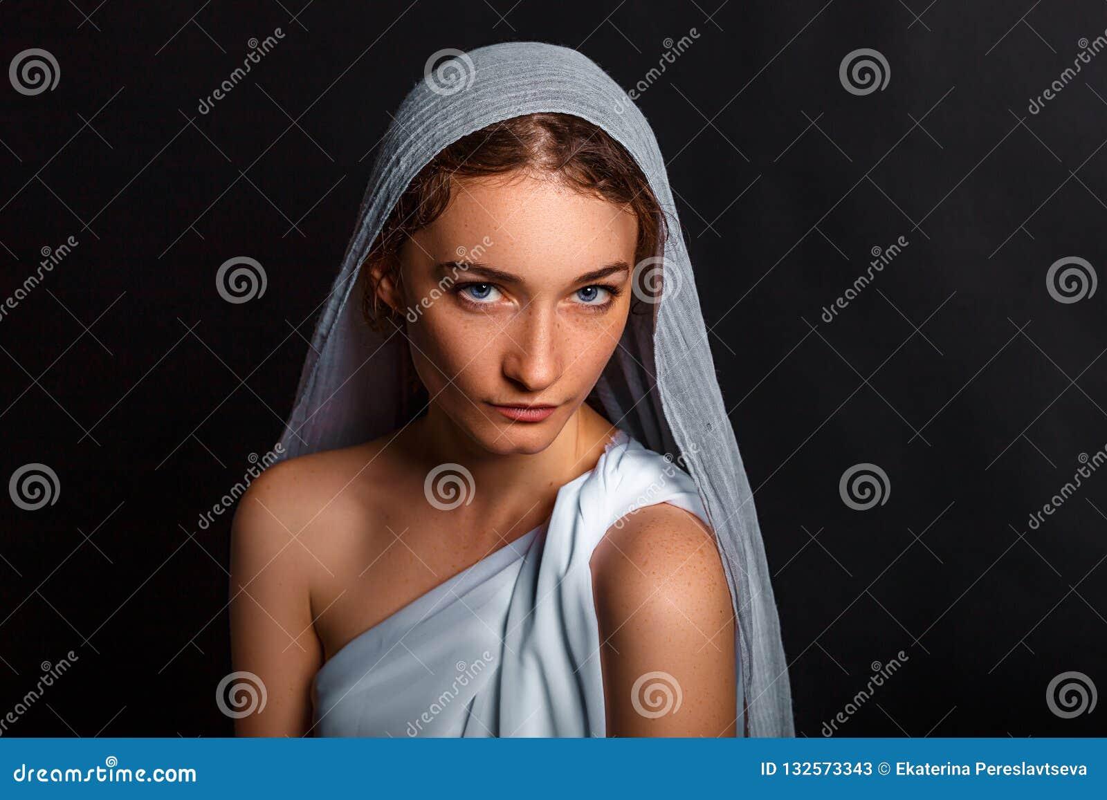 Mooie jonge vrouw met een sjaal op haar hoofd, en een rozentuin in haar handen, bescheiden blik, die vrouw geloven