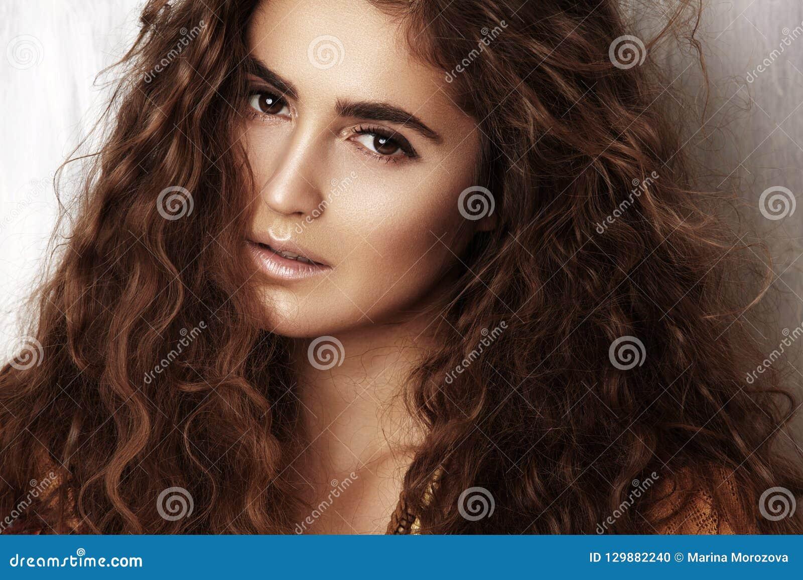 Mooie jonge vrouw met lang krullend kapsel, manierjuwelen met donkerbruin haar De Indische stijlkleren, snakken kleding