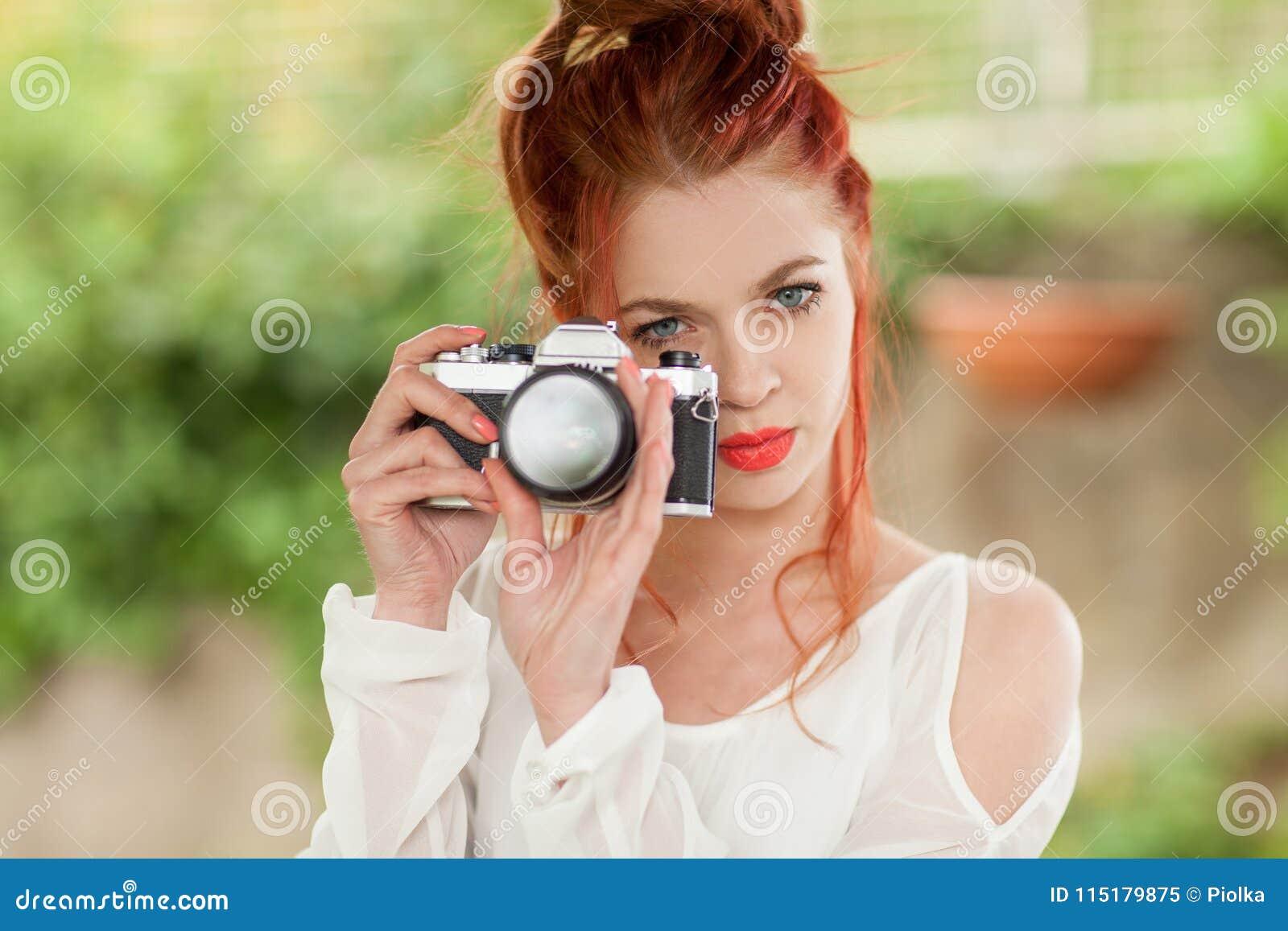 Mooie jonge vrouw met rode haarzitting in de tuin die beelden met camera nemen