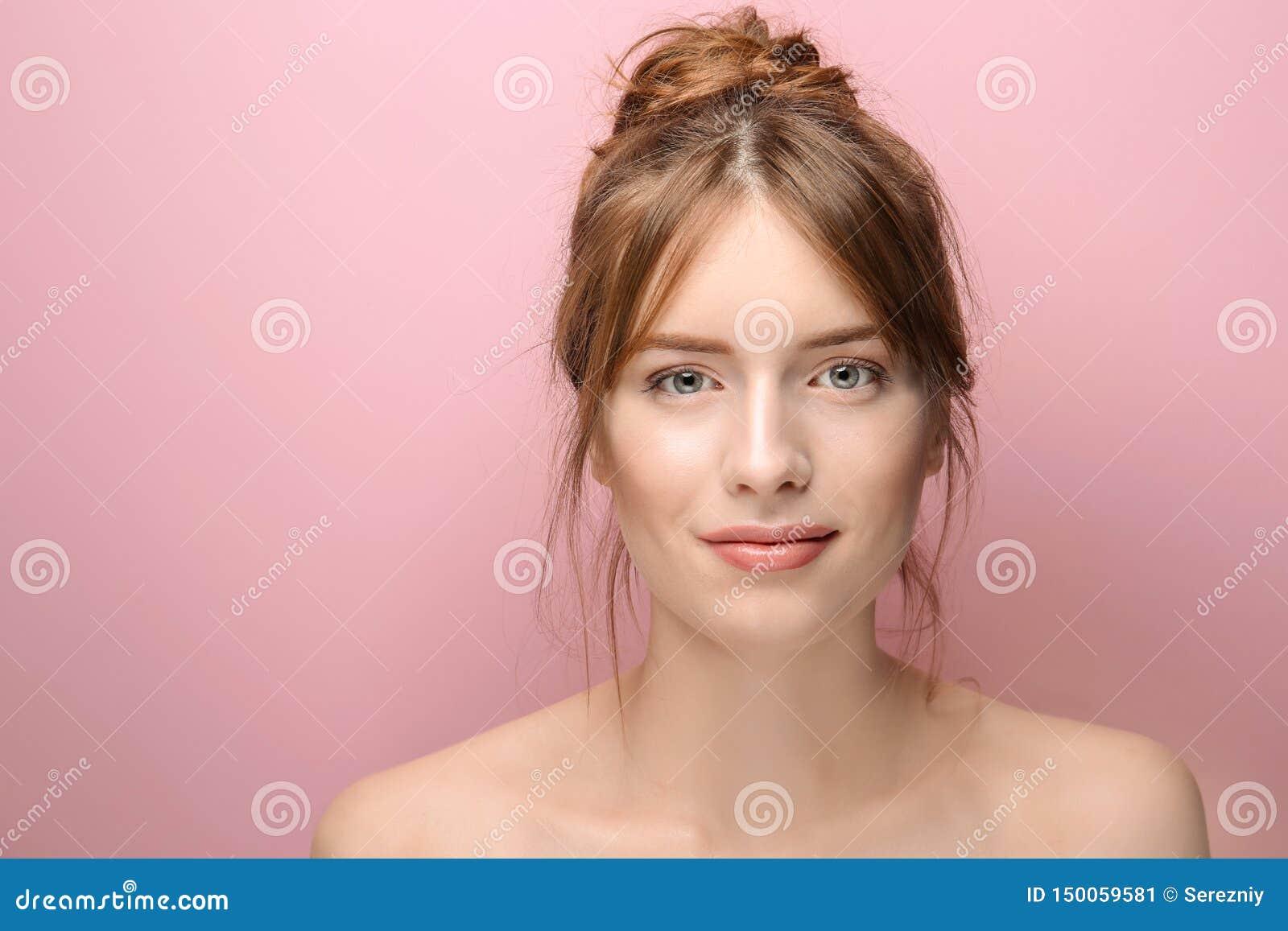Mooie jonge vrouw met zijdeachtige huid op kleurenachtergrond