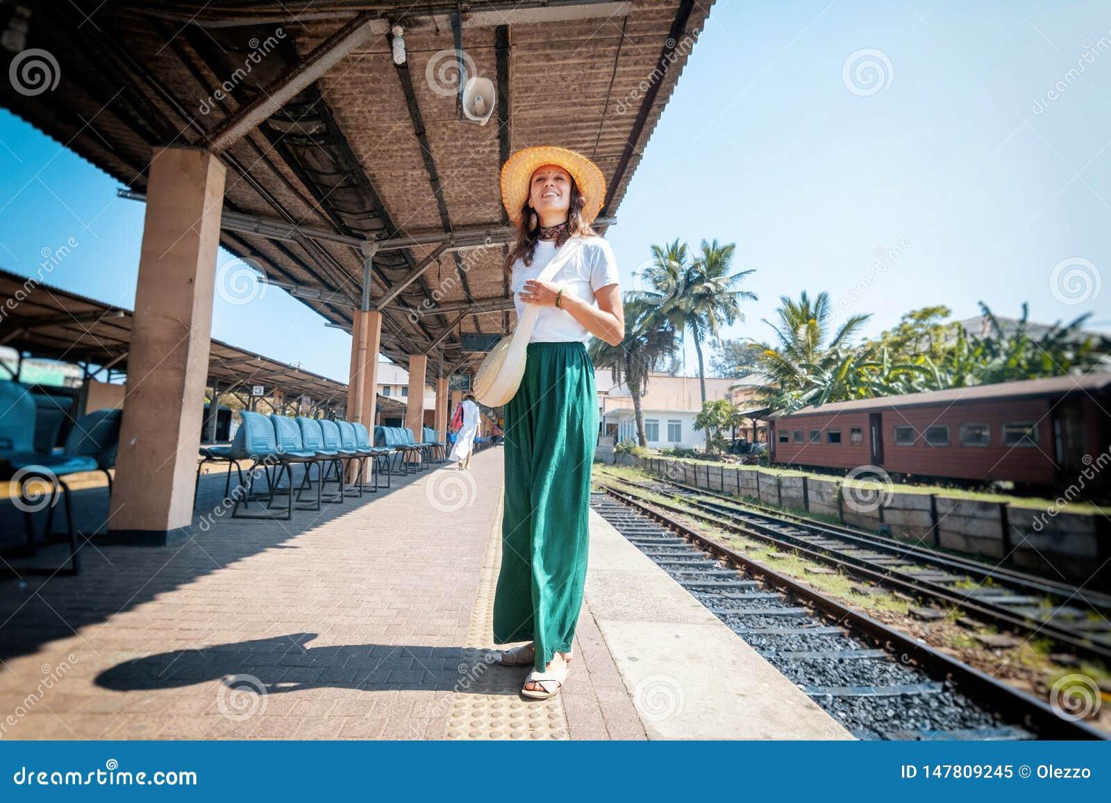 Mooie jonge vrouw in reizigershoed op een spoorwegplatform in Sri Lanka die naar Azië, Ceylon reizen
