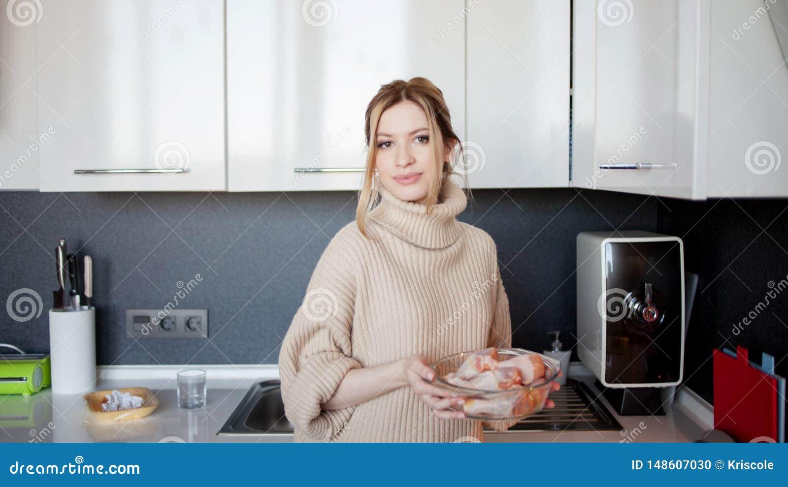Mooie jonge vrouw thuis in de keuken, die een gezonde maaltijd voorbereiden