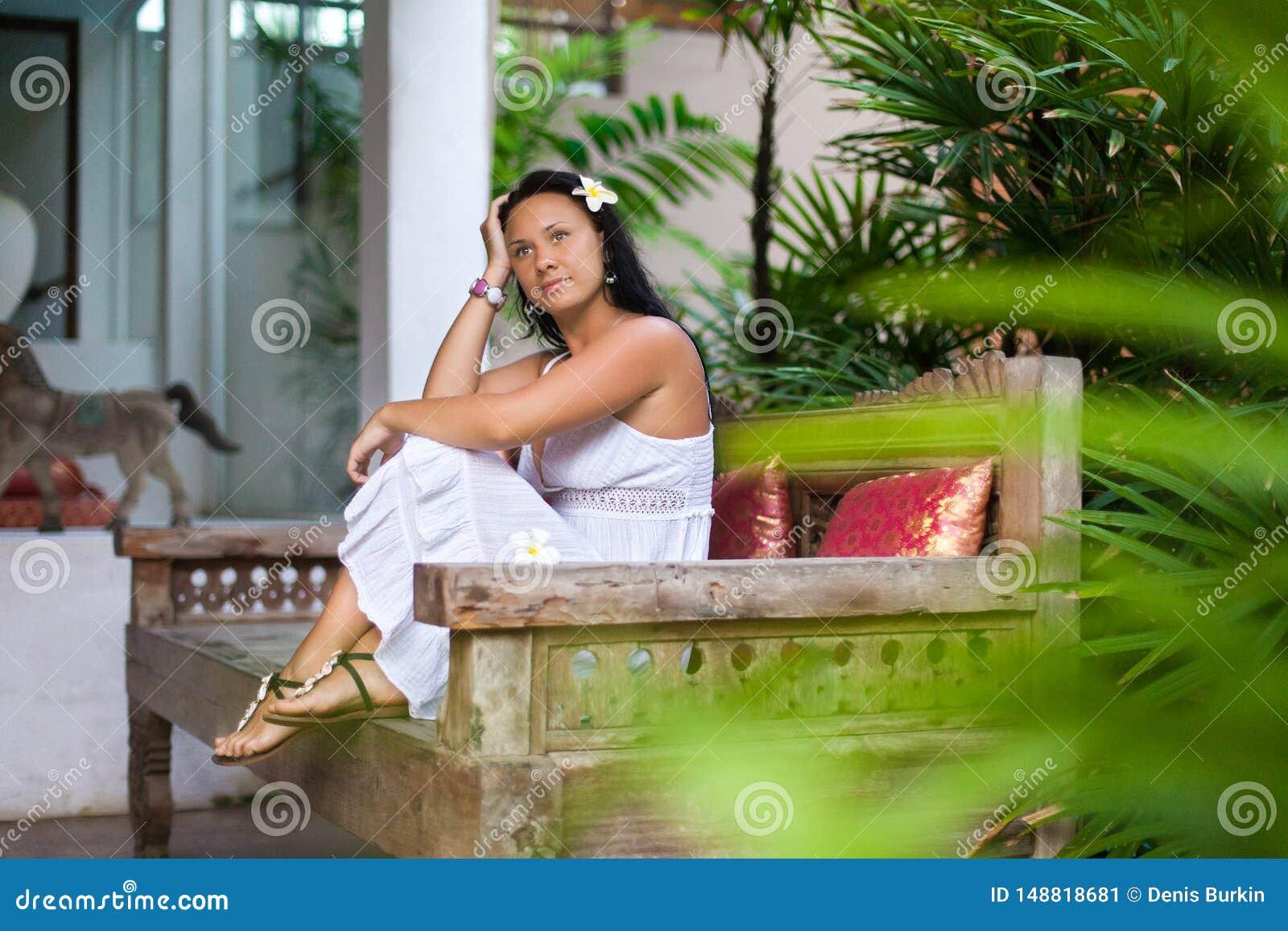 Mooie jonge vrouw in witte kleding die op uitstekende bank in tuin rusten Reis en de zomerconcept