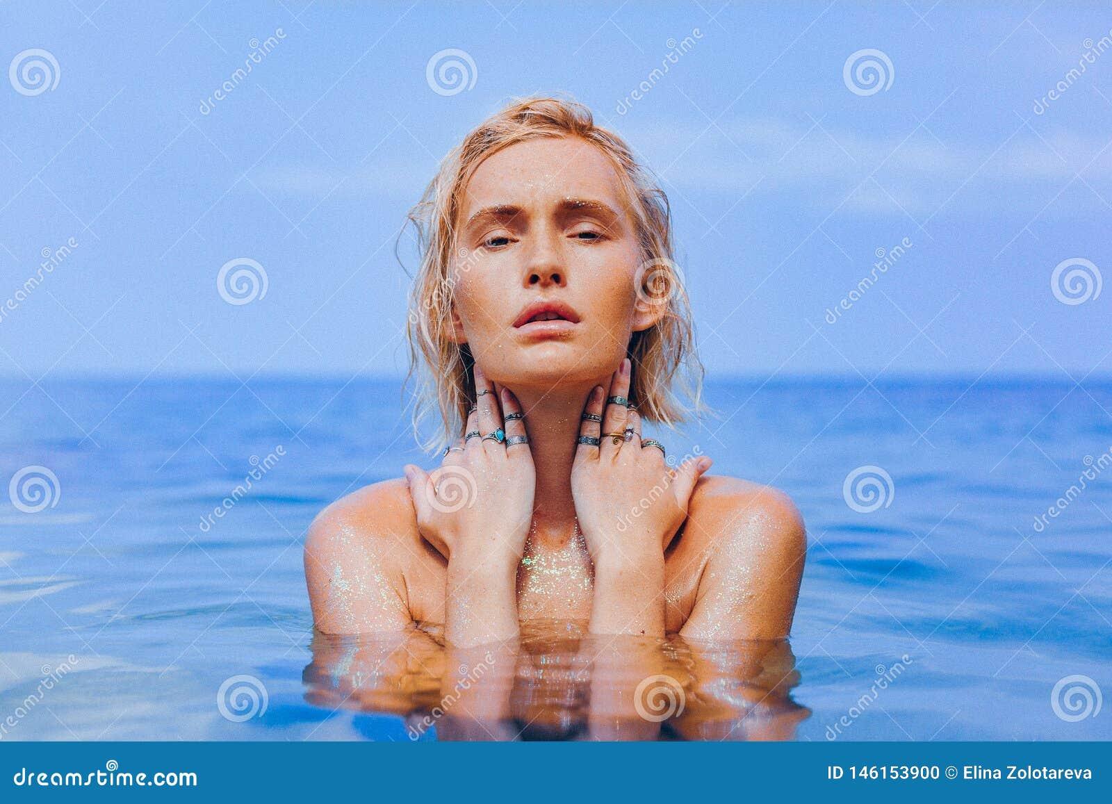 Mooie jonge vrouw in zeewater dicht omhoog sensueel portret