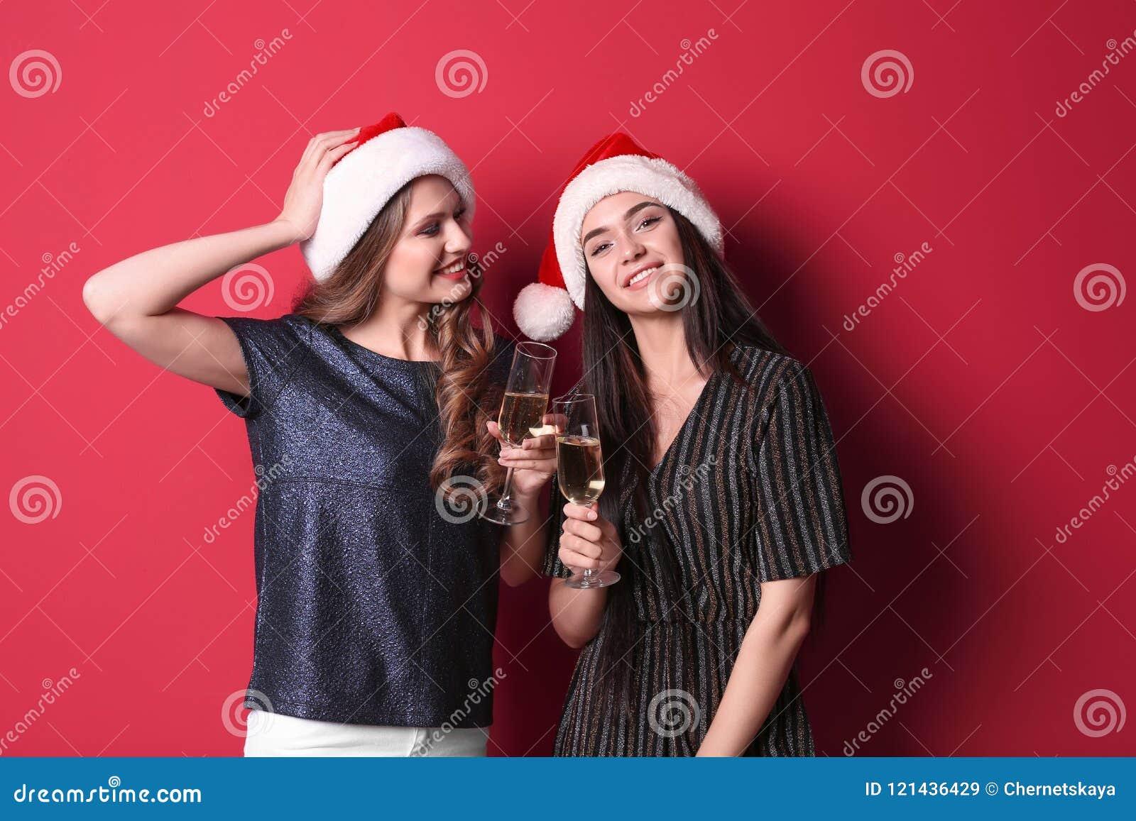 Mooie jonge vrouwen in Kerstmanhoeden met glazen champagne op kleurenachtergrond