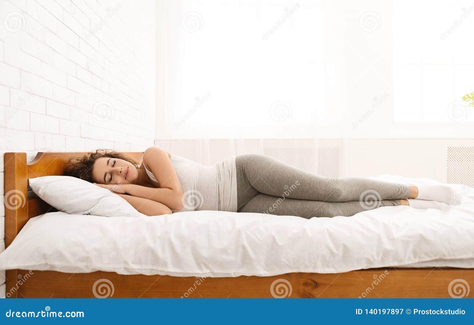 Mooie jonge vrouwenslaap die in haar bed liggen