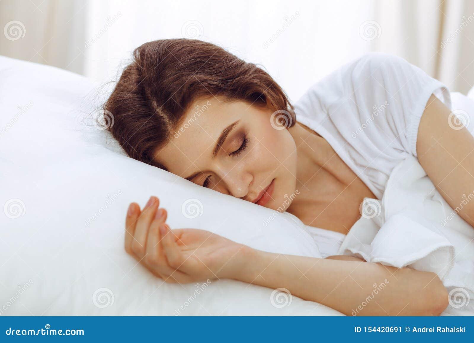 Mooie jonge vrouwenslaap terwijl het liggen in haar bed Concept prettig en rust herstel voor het actieve leven