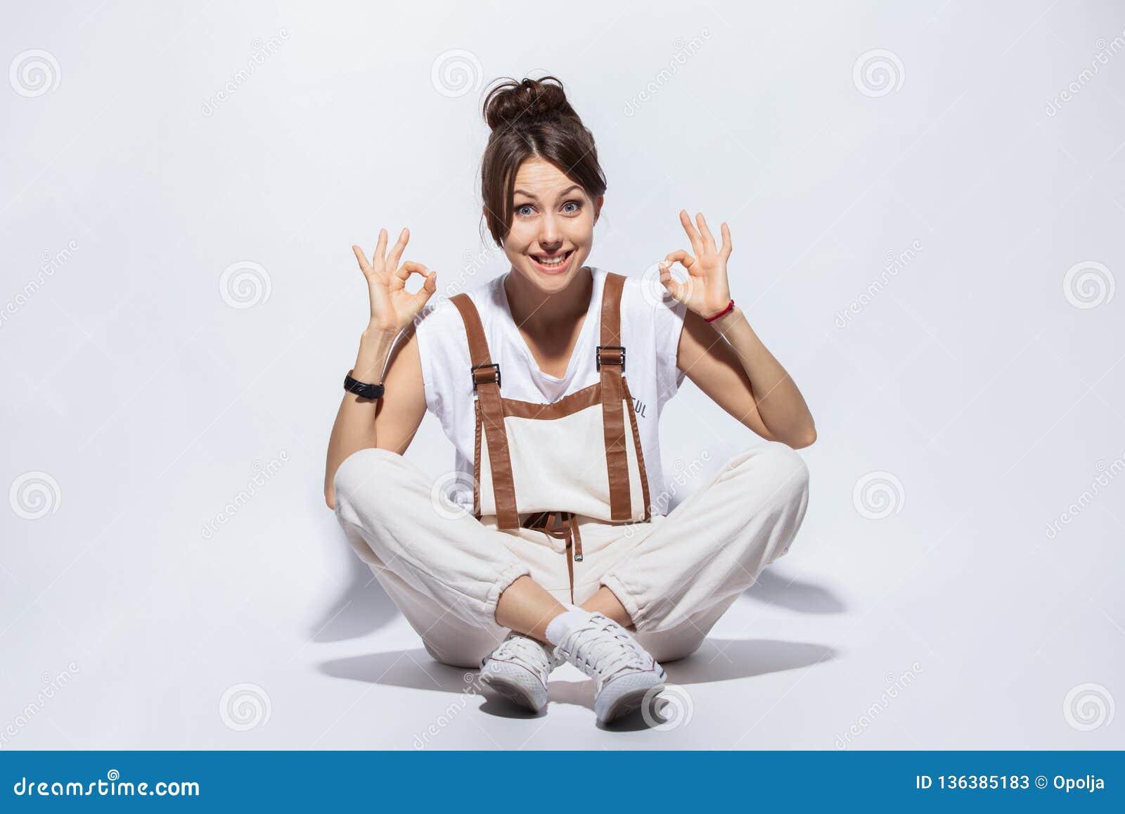 Mooie jonge vrouwenzitting op de vloer, het glimlachen positief, doend o.k. teken met hand en vingers Succesvolle uitdrukking