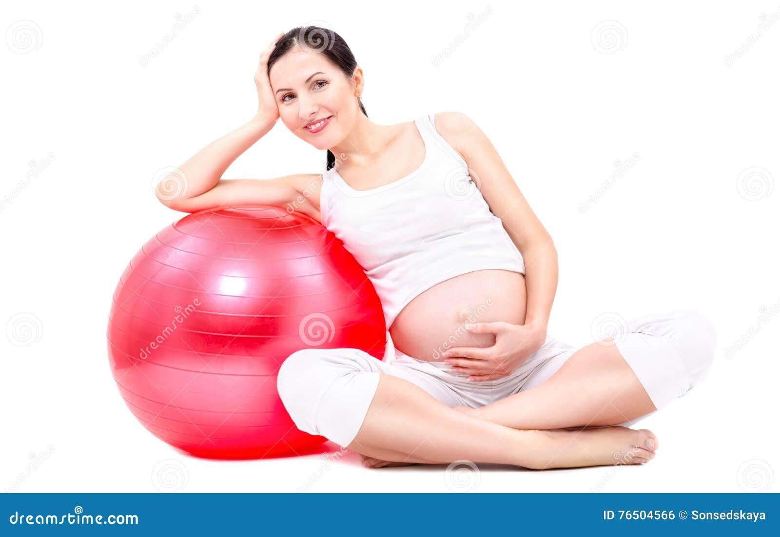 Mooie jonge zwangere vrouwenzitting met fitball
