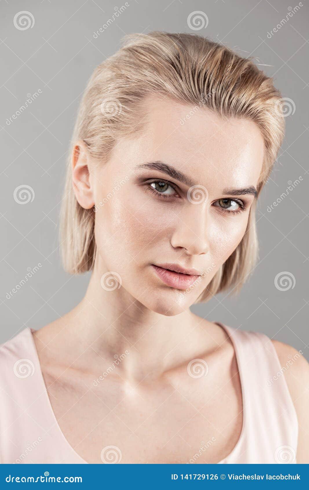 Mooie kortharige vrouw met wreed gezicht en grijze ogen