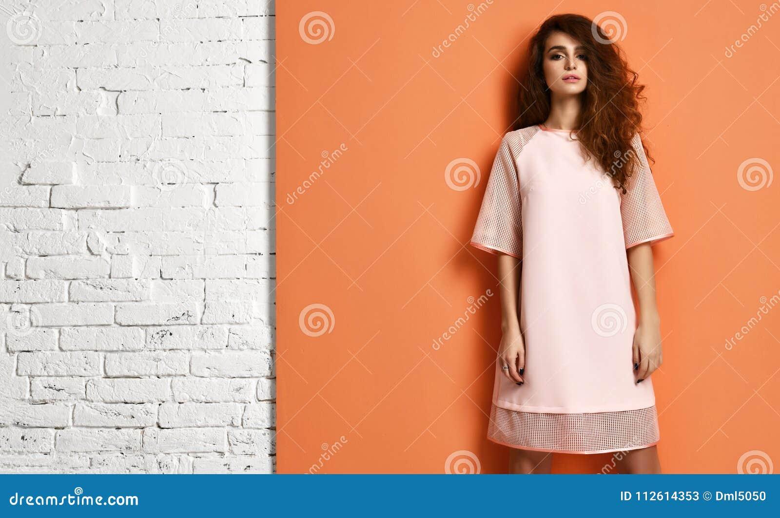 Mooie krullende haarvrouw in pastelkleur roze kleding die zich op sinaasappel en bakstenen muur met tekstruimte bevinden