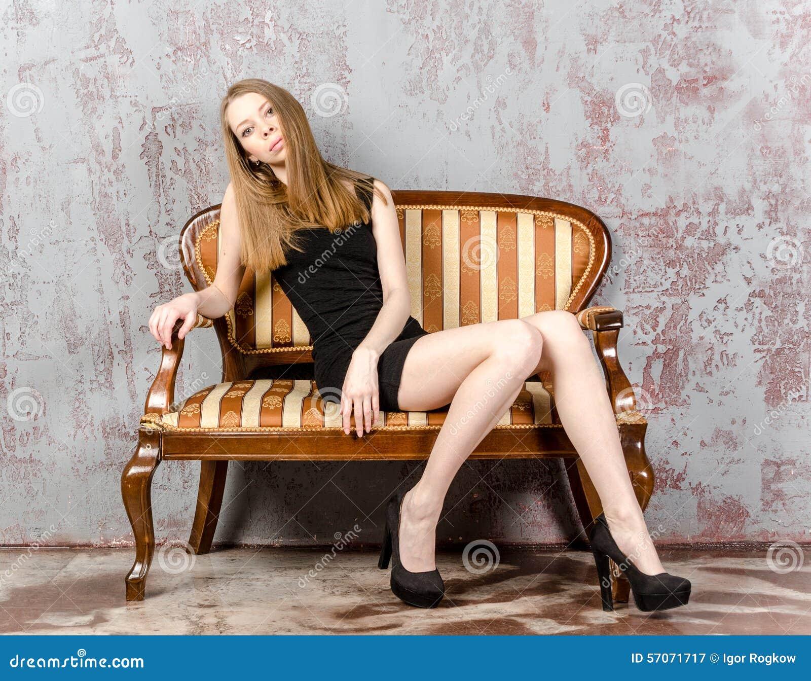Mooie langharige jonge blondevrouw met een slank cijfer in een zwarte minikleding