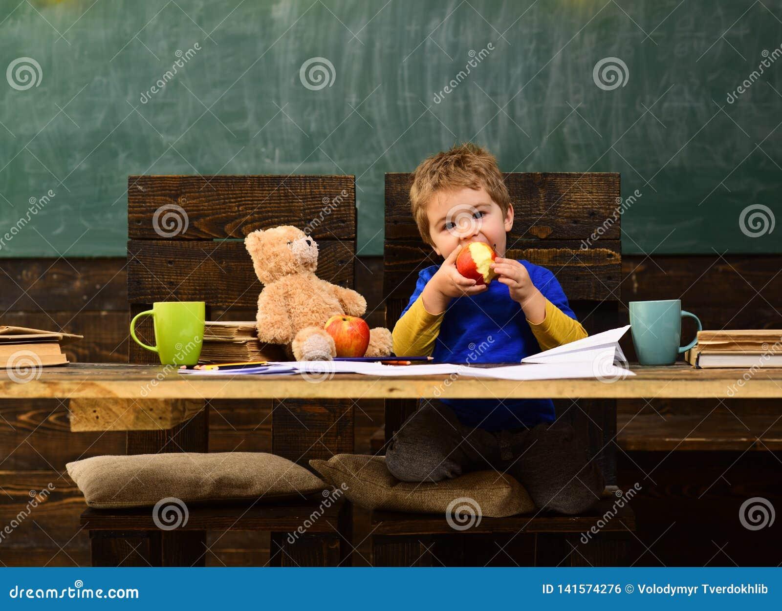 Mooie leraar die leerling in klaslokaal helpen op de basisschool De studenten kunnen tutoring bij bijna elk onderwerp krijgen