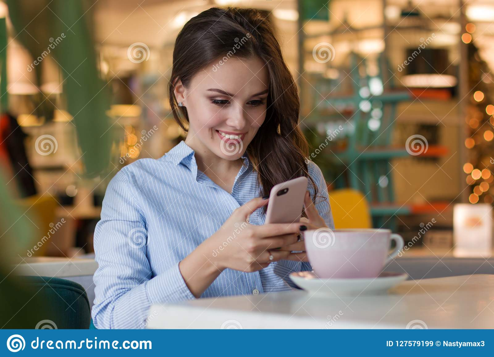 Mooie leuke Kaukasische jonge vrouw in de koffie, gebruikend mobiele telefoon en drinkend koffie het glimlachen