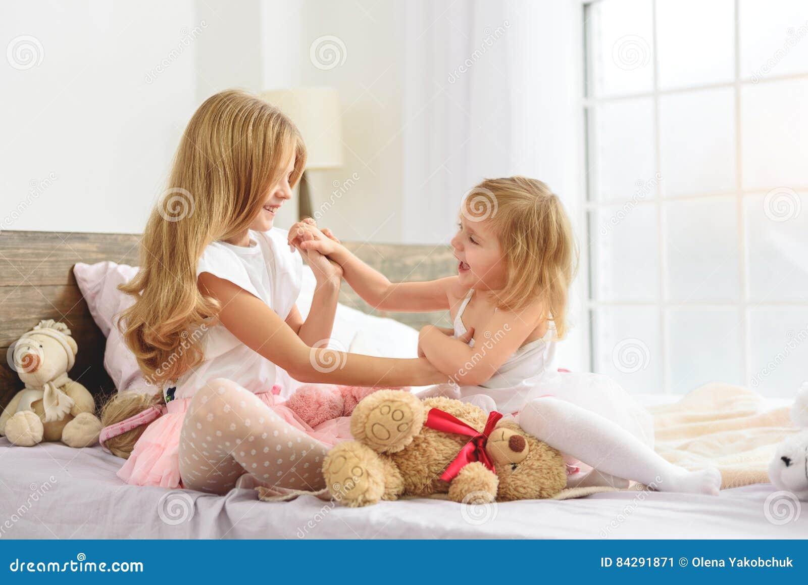 Mooie meisjes die samen in slaapkamer spelen stock foto afbeelding 84291871 for Meisje slaapkamer fotos