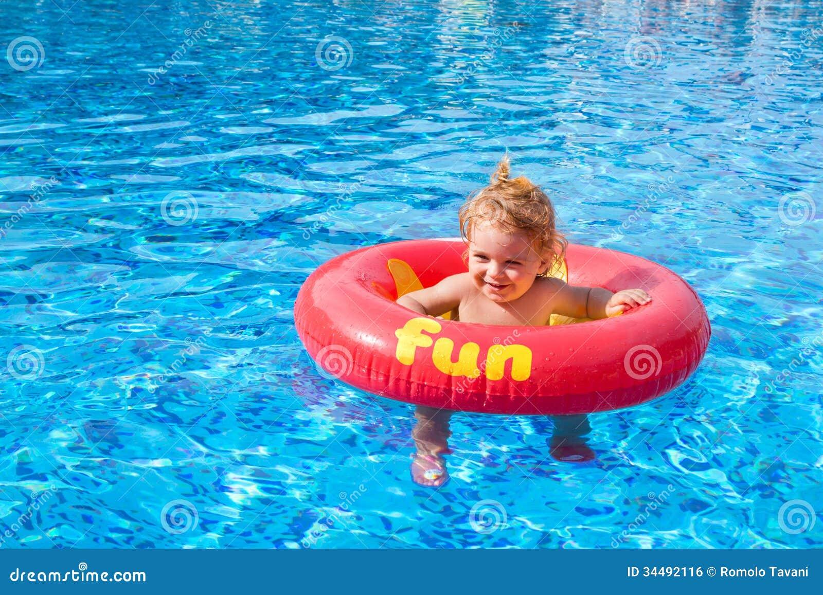 Mooie meisjewhit doughnutvlotter in de pool