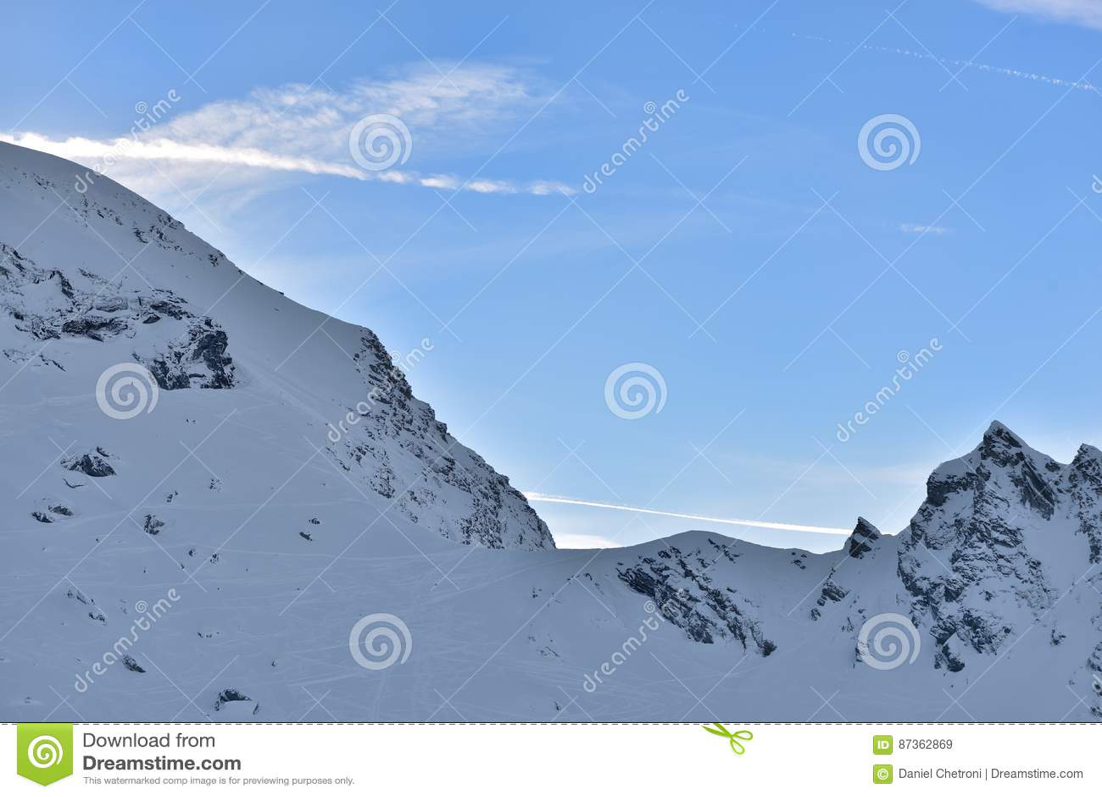 Mooie mening van bergpiek met zonsonderganglicht op bovenkant tegen duidelijke blauwe hemel